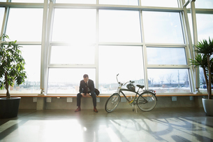 Businessman commuter texting with smart phone next to bicycle in sunny office lobbyの写真素材 [FYI02325267]