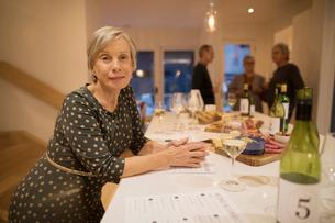 Portrait confident senior woman rating white wine at wine tasting partyの写真素材 [FYI02325276]