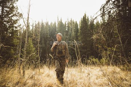Senior hunter in camouflage hunting, walking in remote fieldの写真素材 [FYI02325277]