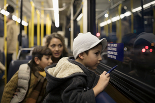 Curious boy riding bus with mother and brother, looking out windowの写真素材 [FYI02325296]
