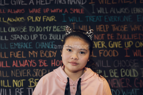 Portrait serious, confident Asian tween girl wearing cat headband against wall with chalk textの写真素材 [FYI02325308]
