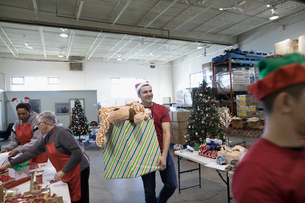 Male volunteer carrying box of Christmas toys in warehouseの写真素材 [FYI02325331]