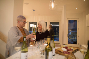 Senior woman showing wine bottle to friend, enjoying wine tasting party social gatheringの写真素材 [FYI02325346]