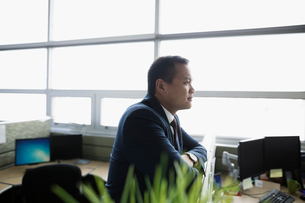 Thoughtful businessman looking away in office cubicleの写真素材 [FYI02325362]