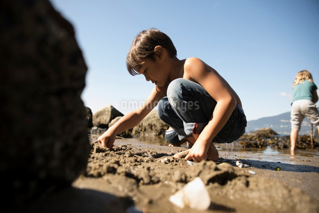 Boy playing in sand on sunny beachの写真素材 [FYI02325371]