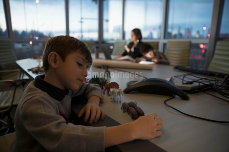 Boy playing with toys and dedicated mother architect working late in conference roomの写真素材 [FYI02325374]