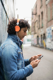 Young man with headphones listening to music with smart phone on urban streetの写真素材 [FYI02325377]