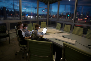 Dedicated mother architect working late with sons coloring in dark conference roomの写真素材 [FYI02325383]