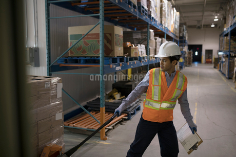 Worker pulling pallet jack with cardboard boxes in distribution warehouseの写真素材 [FYI02325392]