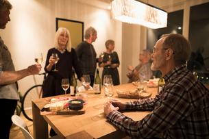 Senior friends enjoying wine tasting party social gathering in dining roomの写真素材 [FYI02325404]