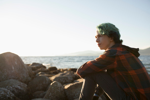 Pensive boy with blue hair sitting on rocks looking at oceanの写真素材 [FYI02325415]