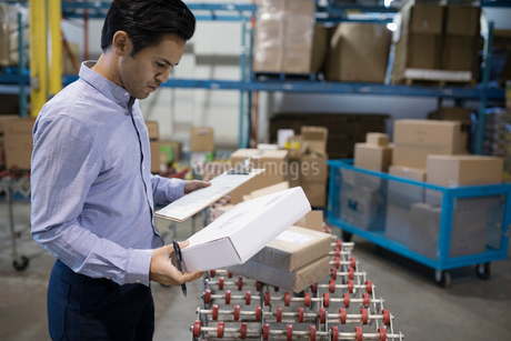 Male warehouse manager with clipboard checking packages on production line conveyor beltの写真素材 [FYI02325418]