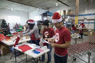 Male volunteer with clipboard wearing Santa hat in warehouseの写真素材 [FYI02325423]