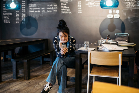 Asian tween girl texting with smart phone at cafe tableの写真素材 [FYI02325436]