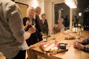 Senior friends enjoying wine tasting party social gathering in dining roomの写真素材 [FYI02325448]