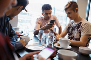 Tween boy friends texting with smart phones at cafe tableの写真素材 [FYI02325451]