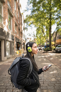 Young woman with backpack and headphones listening to music with smart phone on urban sidewalkの写真素材 [FYI02325454]