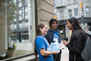 Political young adults canvassing with clipboard, talking to woman on urban sidewalkの写真素材 [FYI02325486]