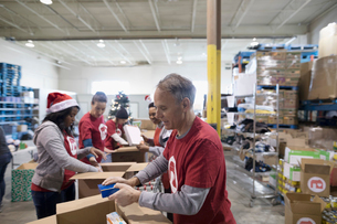 Male volunteer filling Christmas donation boxes in warehouseの写真素材 [FYI02325496]