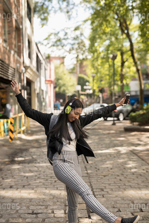 Playful young woman with backpack dancing, listening to music with headphones and smart phone on urbの写真素材 [FYI02325497]