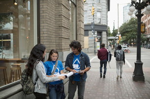 Political young adults canvassing with petitions on urban sidewalkの写真素材 [FYI02325509]
