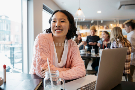 Smiling, confident Korean high school girl student studying at laptop in cafeの写真素材 [FYI02325512]