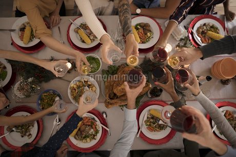 Overhead view family toasting wine glasses at candlelight Christmas turkey  dinner at tableの写真素材 [FYI02325517]