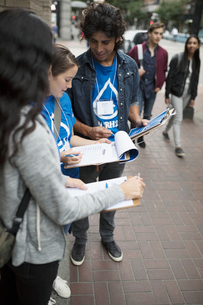 Political young adults canvassing with petitions on urban sidewalkの写真素材 [FYI02325534]