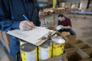 Male volunteer with clipboard managing food drive in warehouseの写真素材 [FYI02325559]