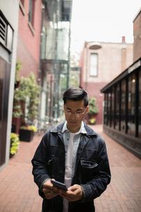 Man texting with smart phone on urban sidewalkの写真素材 [FYI02325562]