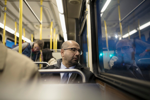 Thoughtful mature businessman commuter riding bus, looking out windowの写真素材 [FYI02325563]