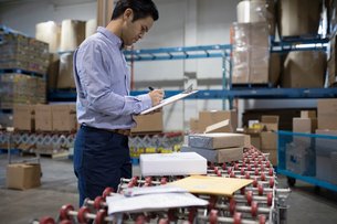 Male warehouse manager with clipboard checking packages on production line conveyor beltの写真素材 [FYI02325569]