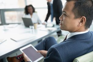 Focused, attentive businessman with digital tablet listening in conference room meetingの写真素材 [FYI02325570]