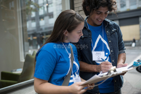 Political young adults canvassing with clipboards on sidewalkの写真素材 [FYI02325575]