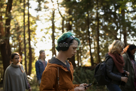 Boy with blue hair listening to music with headphones and mp3 player, hiking in woods with familyの写真素材 [FYI02325579]