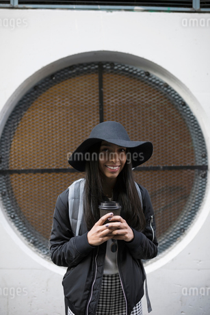 Portrait smiling, confident young woman in hat drinking coffeeの写真素材 [FYI02325605]