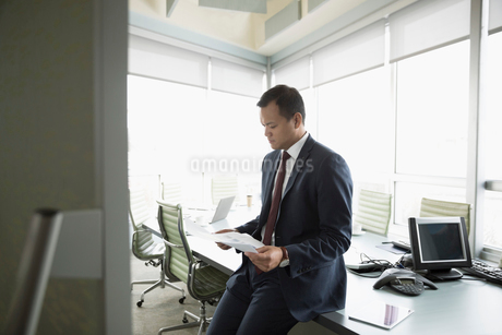 Focused businessman reviewing paperwork, preparing in conference roomの写真素材 [FYI02325613]