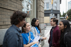 Political young adults canvassing with clipboards, talking to people on urban sidewalkの写真素材 [FYI02325635]