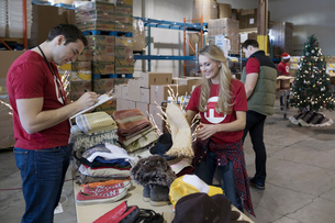 Volunteers sorting Christmas clothing for clothing drive in warehouseの写真素材 [FYI02325647]