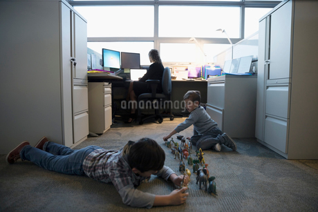 Boys playing with toys on floor near mother businesswoman working in office cubicleの写真素材 [FYI02325648]