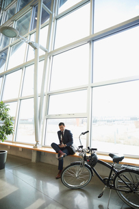 Businessman commuter texting with smart phone next to bicycle in office lobbyの写真素材 [FYI02325673]