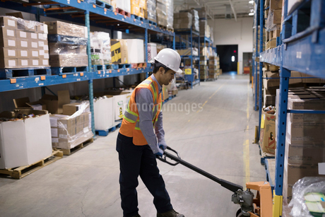 Worker using pallet jack in distribution warehouseの写真素材 [FYI02325704]