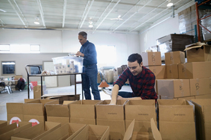 Male volunteer filling donation boxes in warehouseの写真素材 [FYI02325726]