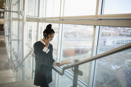 Businesswoman talking on cell phone and checking schedule on office stairsの写真素材 [FYI02325737]