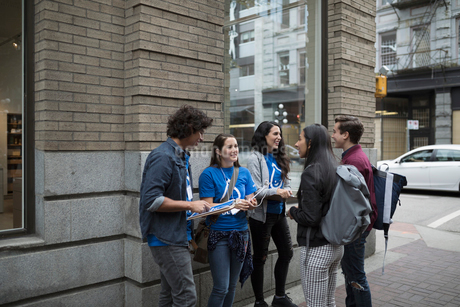 Political young adults canvassing with clipboards, talking to people on urban sidewalkの写真素材 [FYI02325753]