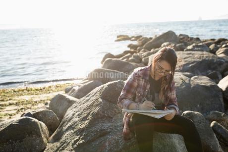 Teenage girl drawing in notebook on rocks on sunny ocean beachの写真素材 [FYI02325768]