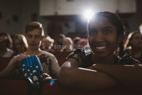 Smiling Indian tween girl watching movie in dark movie theaterの写真素材 [FYI02325780]