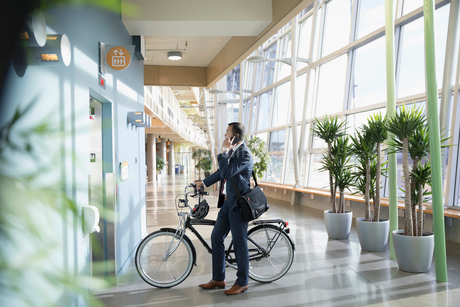 Businessman commuter with bicycle talking on smart phone, waiting at elevator in office lobbyの写真素材 [FYI02325788]
