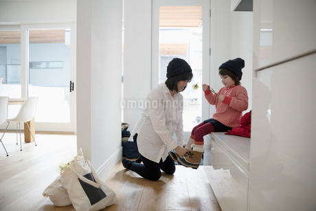 Pregnant mother putting boots on toddler daughterの写真素材 [FYI02325815]