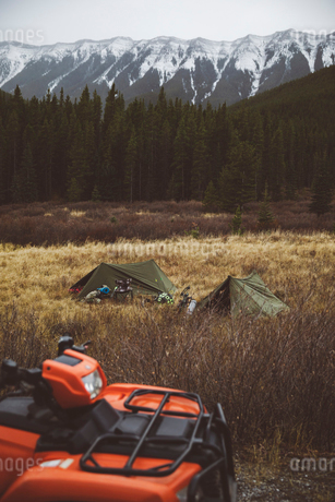 Quadbike and tents at campground in remote field below mountainsの写真素材 [FYI02325824]